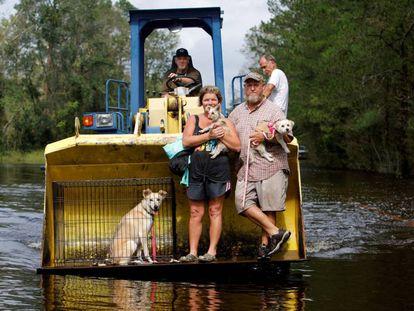 Un hombre evacua a su hermano y a su cuñada junto a sus mascotas tras el desbordamiento del río Cape Fear en Burgaw, Carolina del Norte,