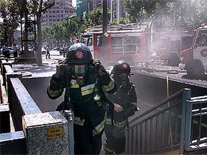 Dos bomberos salen del aparcamiento del paseo de Gràcia de Barcelona tras participar en la extinción de un incendio.