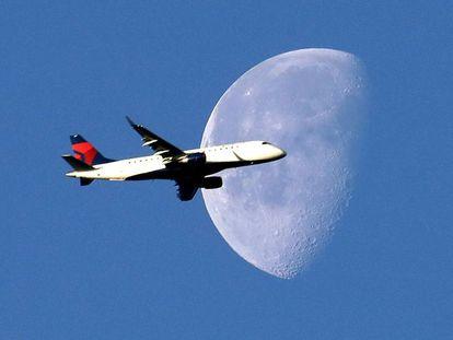 Un avión cruza el cielo ante la luna.