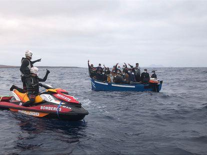 Dos bomberos indican a 24 inmigrantes de una patera localizada frente a la costa de Pedro Barba, en La Graciosa (Canarias), que esperen a un barco de Salvamento Marítimo.