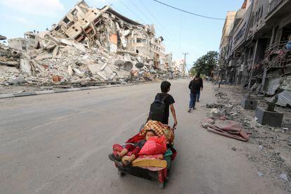 Un niño traslada a su hermano entre los escombros de los edificios bombardeados en Gaza, este viernes.