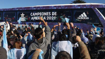 Los aficionados de Argentina celebran a los futbolistas de la selección subidos en el camión, este domingo.