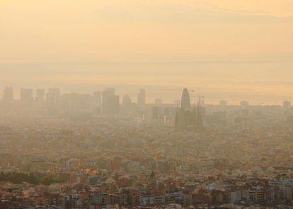 Vista aérea de Barcelona, con la Sagrada Familia y la Torre Agbar en el centro, apenas visibles por la contaminación atmosférica.