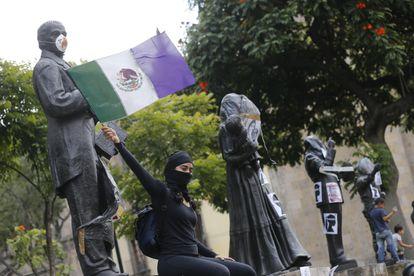 Una feminista alza una bandera intervenida en la denominada 'antigrita' de la Independencia, en Jalisco.