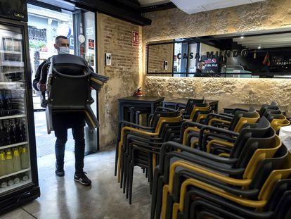 El personal de un local de hostelería de Valencia recoge las sillas para cerrar por las medidas tomadas contra el coronavirus.