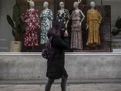 Una mujer pasa por delante de una tienda cerrada en la Gran Vía de Madrid.