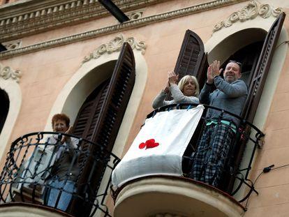 Vecinos de L'Hospitalet (Barcelona) aplauden en sus balcones este martes.