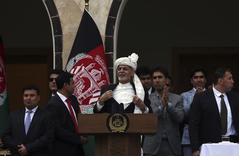 Ashraf Ghani, en el centro, abre su chaqueta después de que dos cohetes alcanzasen el perímetro del palacio presidencial de Kabul, este lunes, durante su discurso.