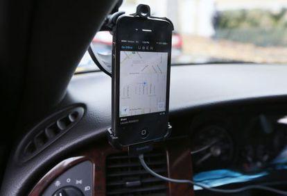Un móvil instalado en un coche muestra la aplicación de Uber