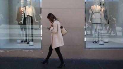 Una mujer pasa por delante de los escaparates de una tienda, en Madrid.