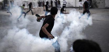 Un manifestante lanza un bote de gas a los antidisturbios durante una protesta en Manama.