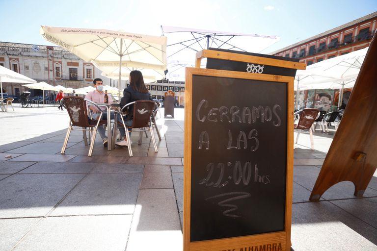 Una pizarra anuncia el nuevo horario de uno de los bares de la Plaza de la Corredera en Córdoba.