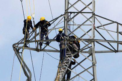 Varios operarios reparan una torre de tendido eléctrico en Girona.
