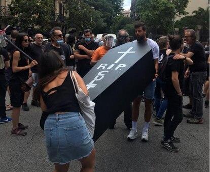 Dos manifestantes cargan un ataúd con la leyenda 'RIP Cultura'.