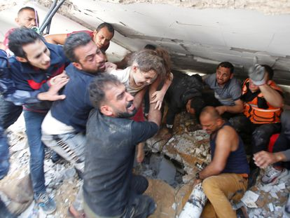 Unos ciudadanos rescataban a una niña de entre los escombros de un edificio derruido, este domingo en la ciudad de Gaza.