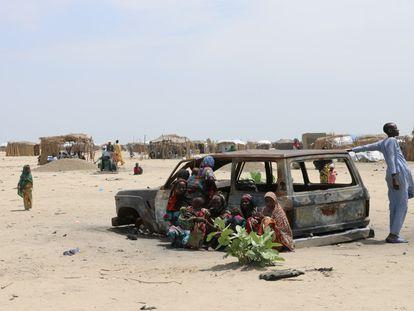 Jóvenes en Diameron, en el Lago Chad, junto a un coche quemado.