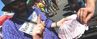 Un manifestante ofrece dinero falso en la protesta contra el G-8 en Lecce (Italia).