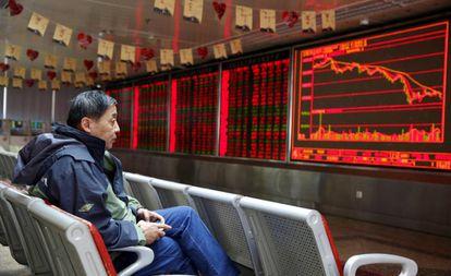 Un hombre observa un panel de información bursátil en Pekín (China).