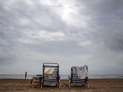 Dos hamacas solitarias bajo un cielo nublado en la playa de la Malvarrosa de Valencia, este jueves.