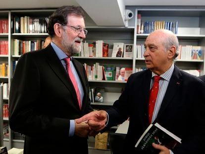 El expresidente del Gobierno Mariano Rajoy conversa con el exministro del Interior Jorge Fernández Díaz en una presentación de un libro en octubre de 2019 en Madrid.