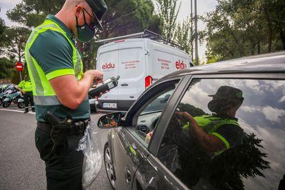 Un policía para a unos coches para someter a pruebas de control de consumo de drogas y alcohol a los conductores durante la presentación de una nueva campaña de la DGT, este miércoles.
