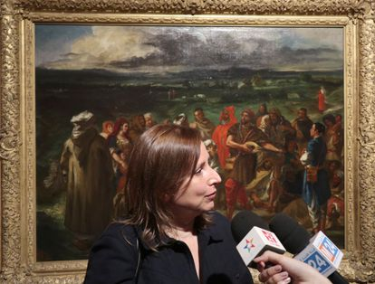 The curator of the exhibition and director of the Delacroix Museum, Claire Bessède, attends the media with a painting of the exhibition behind.