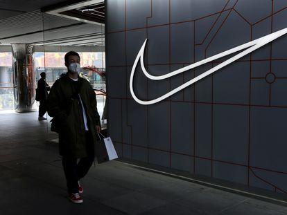Un hombre camina junto a una tienda de Nike.