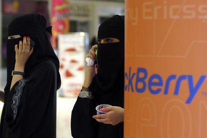 Dos mujeres hablan por sus Blackberrys en un centro comercial de Riad (Arabia Saudí).