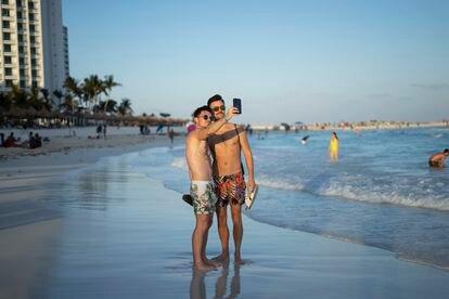 Una pareja de turistas se toma una foto el pasado mes de abril en la playa de Cancún (Quintana Roo), donde operaba y residía el presunto líder de la mafia rumana Florián Tudor.