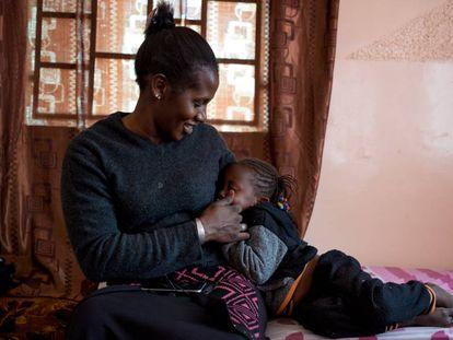 Mbayam Diop, de 30 años y esposa de emigrante, acaricia a su hija Mamita en el salón de su vivienda en Gandiol, en el distrito senegalés de Saint Louis.