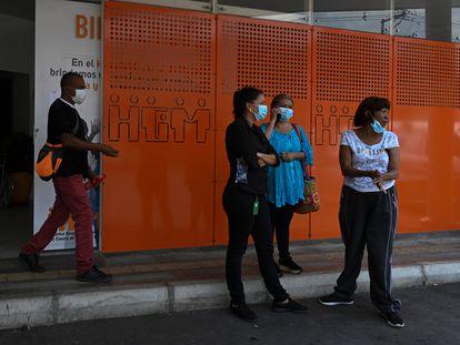 Un grupo de personas espera frente a un hospital en Medellín, Colombia.