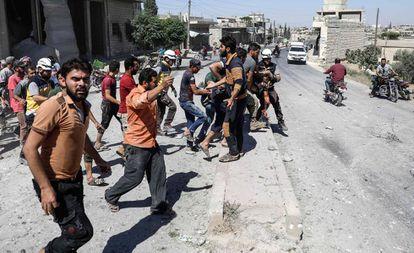 Civiles y miembros de la Defensa Civil Siria trasladan un cuerpo en la provincia de Idlib.