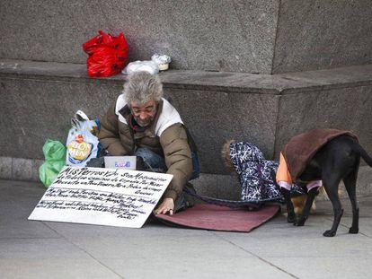 Una persona sin hogar con dos perros, en una calle de Madrid.