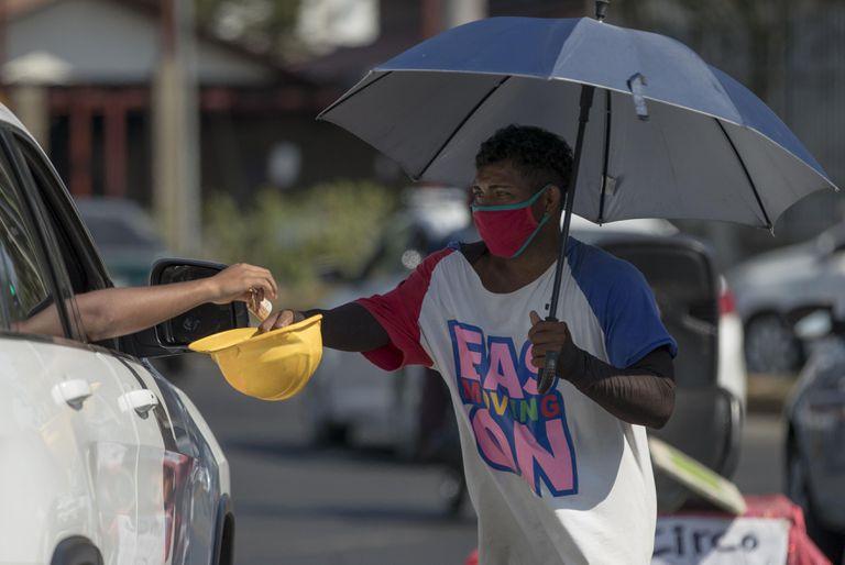 Un artista callejero recibe dinero tras actuar en una calle el pasado viernes, en Managua (Nicaragua).