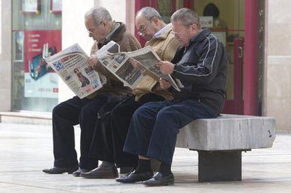 Un grupo de jubilados lee la prensa en una calle peatonal de Málaga.