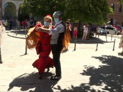 Una pareja vestida de chulapos bailando frente a la iglesia de la Virgen de la Paloma y San Pedro el Real en el día de su fiesta, en agosto.