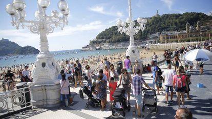 Los turistas pasean por el centro de San Sebastian.