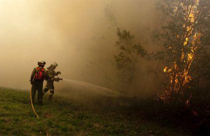 Los bomberos, durante las labores de extinción de un incendio en el pueblo de AS Paradellas (Ourense).