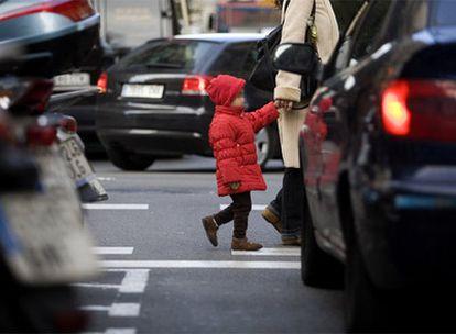 Una niña pasa a la altura de los tubos de escape de los coches, en una calle de Barcelona.
