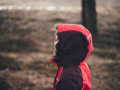 Un niño camina bajo la lluvia.