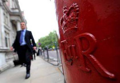En la imagen, un peatón caminando junto a un buzón de correos en Londres (Reino Unido). EFE/Archivo