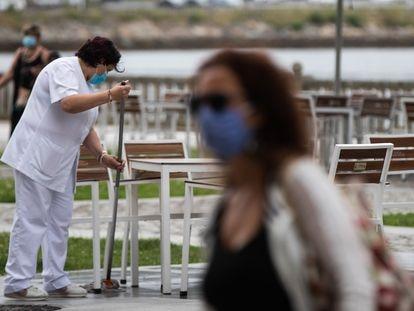 Una trabajadora de un hotel desinfecta la calle donde se encuentra la terraza en el centro de Viveiro, en A Mariña (Lugo).