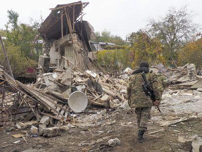 Un soldado armenio examina una casa destruída por la artillería de Azerbaiyán en Stepanakert.