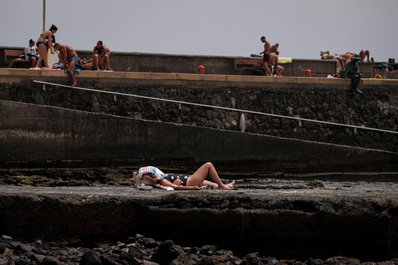 Una mujer toma el sol en una rampa para pequeñas embarcaciones en la playa de Arinaga, en el municipio grancanario de Agüimes.