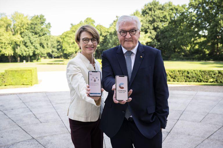 El presidente de Alemania, Frank-Walter Steinmeier, junto a su mujer, Elke Buedenbender, posan con sus móviles con la nueva app alemana de rastreo de contagios, Corona Warn, en las pantallas.