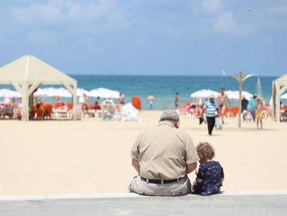 Un abuelo se sienta con su nieta en el poyete de un paseo marítimo.