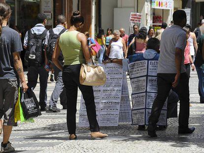 Una mujer negra mira ofertas de trabajo en una calle de São Paulo