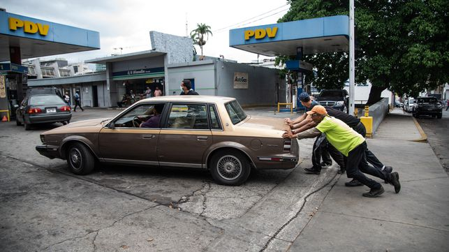 Unos hombres empujan un coche a la entrada de una gasolinera, en junio, en Caracas.