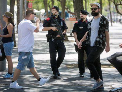 Patrulla de los mossos con armas largas por el Paseo Juan de Borbón de la Barceloneta.