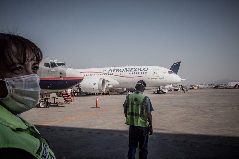 Trabajadores de Aeroméxico delante de un avión en el Aeropuerto Internacional de Ciudad de México.